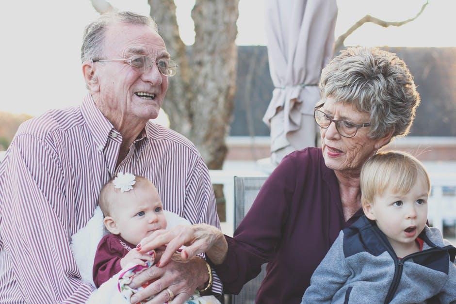 grands-parents avec leurs petits-enfants sur les genoux